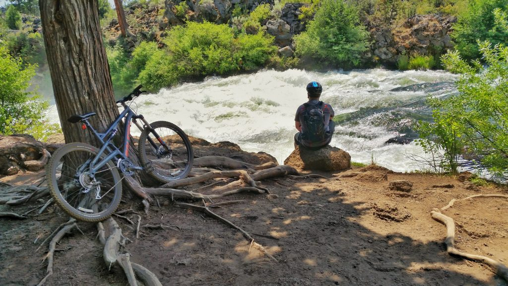 Sitting by the Deschutes River during a trail ride